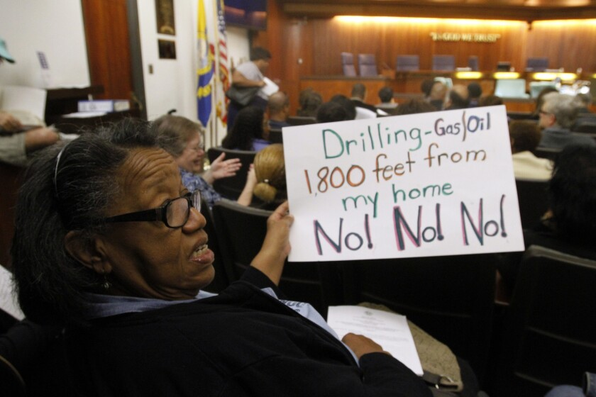 Before a Carson City Council meeting in March, Frances Haywood holds a sign protesting new oil and gas production. California Resources, which was seeking to drill 200 wells to extract oil from the Dominguez Oil Field, announced Monday that it is dropping the project.