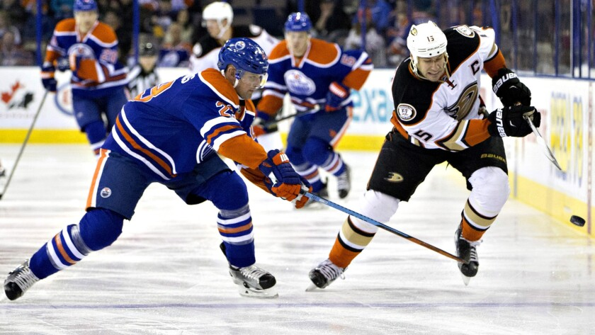 Ducks center Ryan Getzlaf (15) and Oilers winger Matt Hendricks (23) battle for the puck during the first period Thursday night.