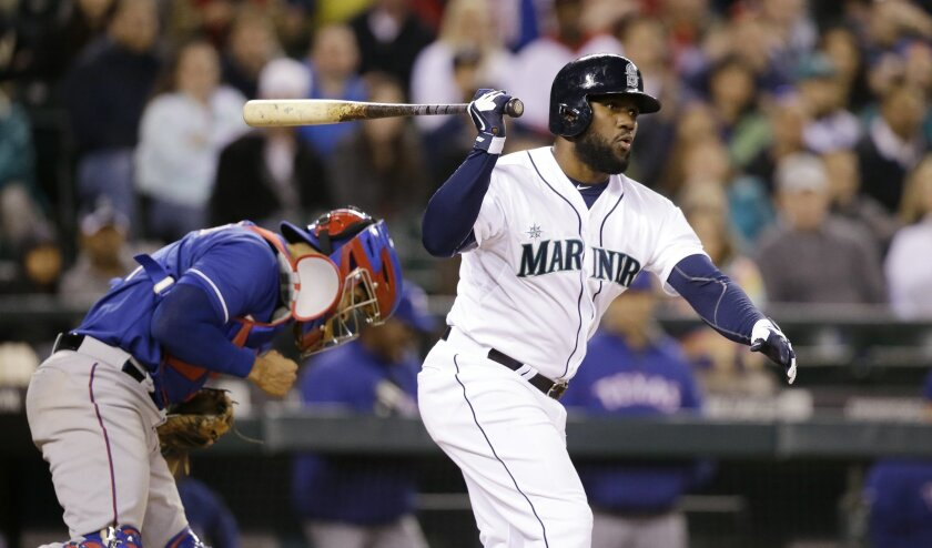 Seattle Mariners' Abraham Almonte swings and misses to strike out and end the baseball game in the ninth inning as Texas Rangers catcher Robinson Chirinos pumps his fist and heads to the mound Saturday, April 26, 2014, in Seattle. The Rangers won 6-3. (AP Photo/Elaine Thompson)