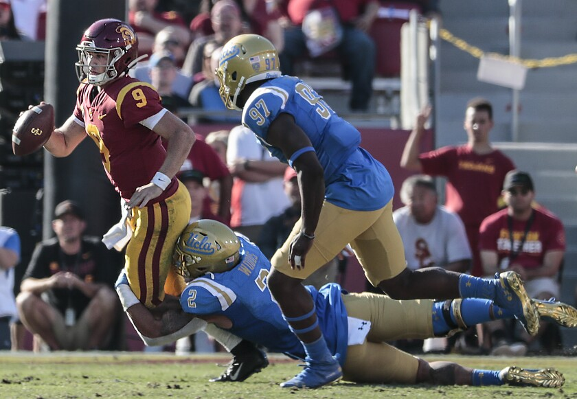 UCLA linebacker Josh Woods (2) tackles USC quarterback Kedon Slovis (9) during a fourth quarter drive at the Coliseum on Saturday.