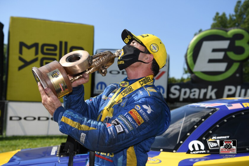Ron Capps kisses the trophy recently won at the Dodge NHRA Indy Nationals presented by Pennzoil.