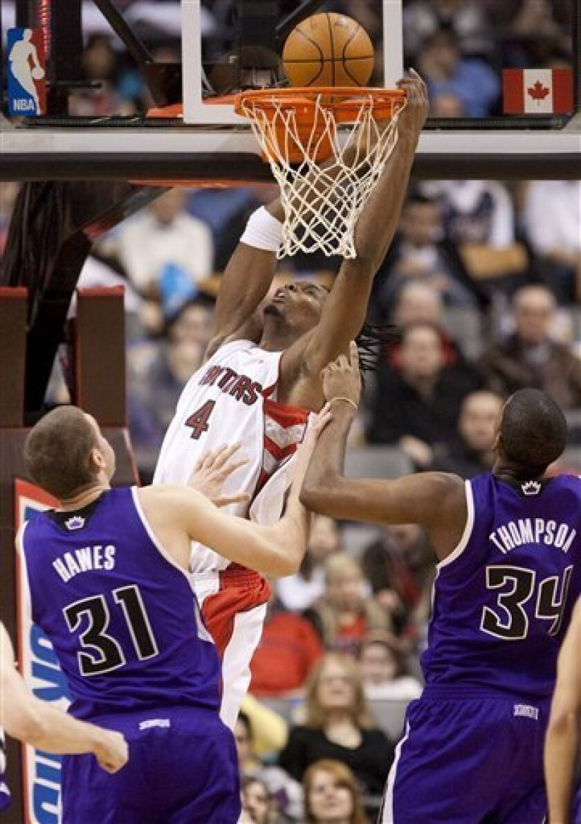 Toronto Raptors' Chris Bosh (4) dunks over Sacramento Kings' Spencer Hawes (31) and Jason Thompson (34) during the first half of an NBA basketball game in Toronto, Sunday, Feb. 7, 2010. (AP Photo/The Canadian Press, Darren Calabrese)