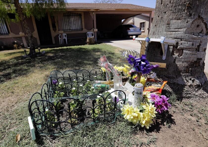 ARCHIVO - En esta fotografía de archivo del 27 de julio de 2016 puede apreciarse un monumento conmemorativo improvisado afuera de la casa donde un presunto asesino serial asesinó a un hombre anteriormente en el año en Phoenix. Las autoridades han dado a conocer reportes policiales sobre dos de siete muertes a balazos que las autoridades creen fueron efectuadas por un asesino serial. Los reportes detallan las muertes a tiros de Manuel Castro García y Horacio de Jesús Peña, que fallecieron con una semana de diferencia en junio en el vecindario Maryvale de la ciudad. (AP Foto/Matt York, archivo)