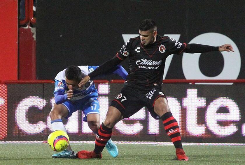 El jugador Gustavo Bou (d) de Xolos disputa el balón con Alonso Zamora (i) de Puebla el viernes 26 de enero de 2018, durante el juego correspondiente a la jornada 4 del torneo mexicano de fútbol celebrado en el estadio Caliente en la ciudad de Tijuana (México). EFE