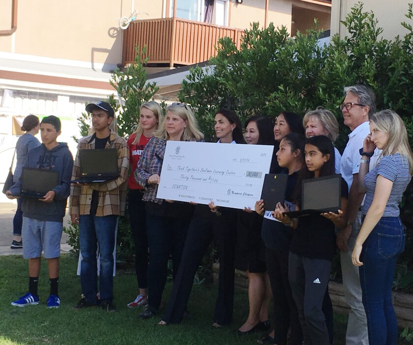 Members of the Newport Chapter of the National Charity League present a $30,000 check Wednesday to the Think Together Shalimar Learning Center for a new coding program.