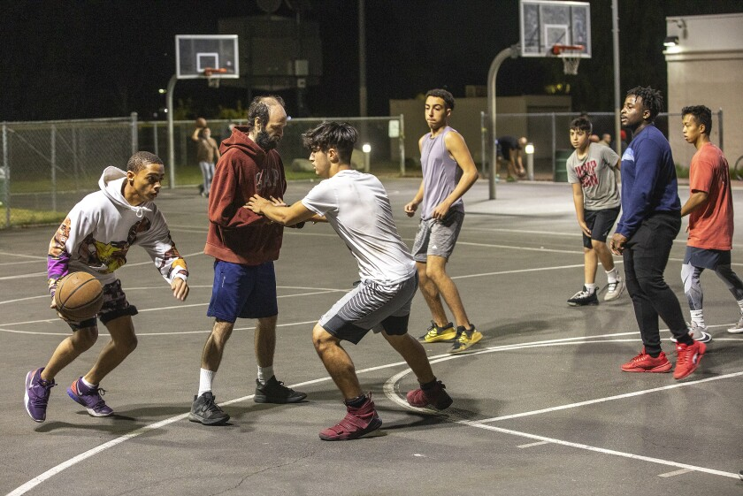 People play basketball without protective masks on at Reseda Park in Reseda.