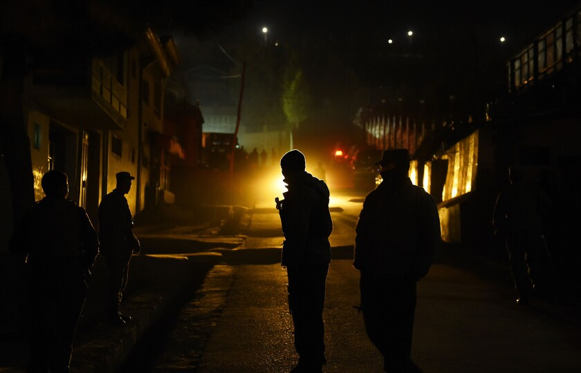 Afghan police officers guard the site of a suicide attack on the Kabul offices of the nonprofit group International Relief and Development on Nov. 27.