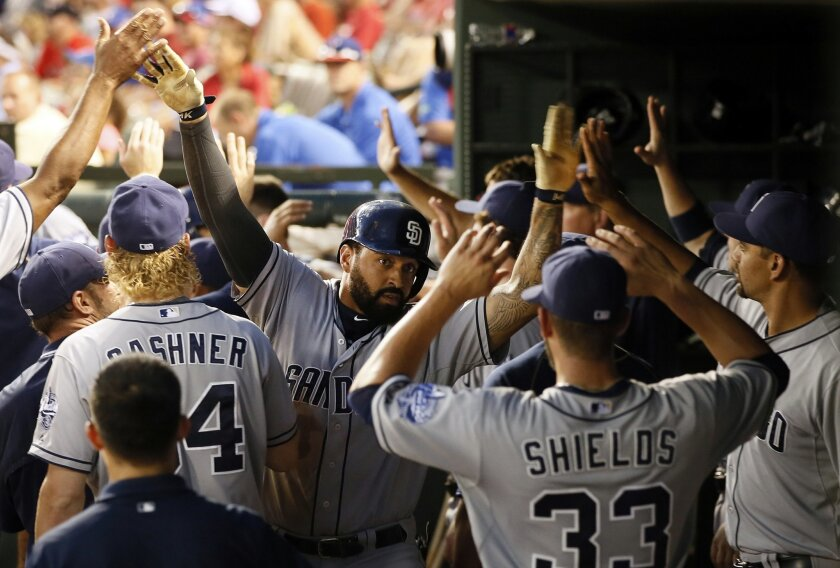 San Diego Padres' Matt Kemp, center, is congratulated by James Shields (33) and others in the dugout after Kemp hit a two-run home run off of Texas Rangers' Colby Lewis during the third inning of an interleague baseball game Saturday, July 11, 2015, in Arlington, Texas. (AP Photo/Tony Gutierrez)