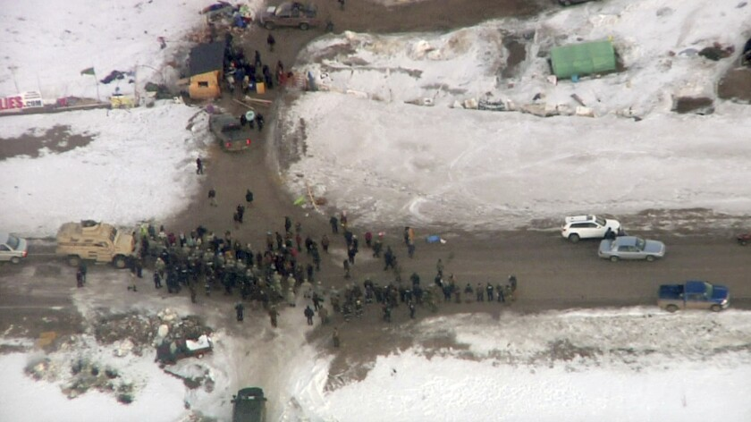 In this Wednesday, Feb. 1, 2017, aerial image taken from a video by KXMB in Bismarck, N.D., law enforcement officers line up against protesters during the eviction of about 40 Dakota Access pipeline opponents from a camp on private property owned by the pipeline developer where the protesters set up on higher ground near their flood-prone main camp in southern North Dakota near Cannon Ball, N.D.
