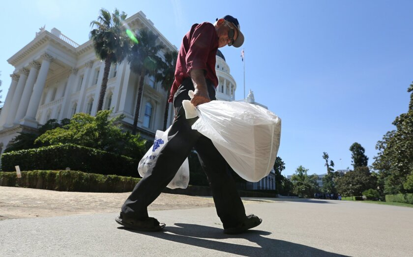 FILE - In this Aug. 12, 2014 file photo, a man carries plastic single-use bags past the State Capitol in Sacramento, Calif. Starting in July 2015, California will become the first state to ban single-use plastic bags under a new law passed by the Legislature and signed by Gov. Jerry Brown in 2014.