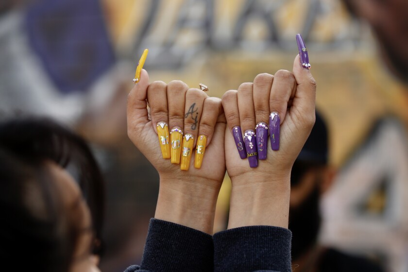 Jazmine Jabi shows off designer nails she created to honor Kobe Bryant at a mural on Lebanon Street, a short distance from Staples Center, where a memorial for the Lakers star was taking place.