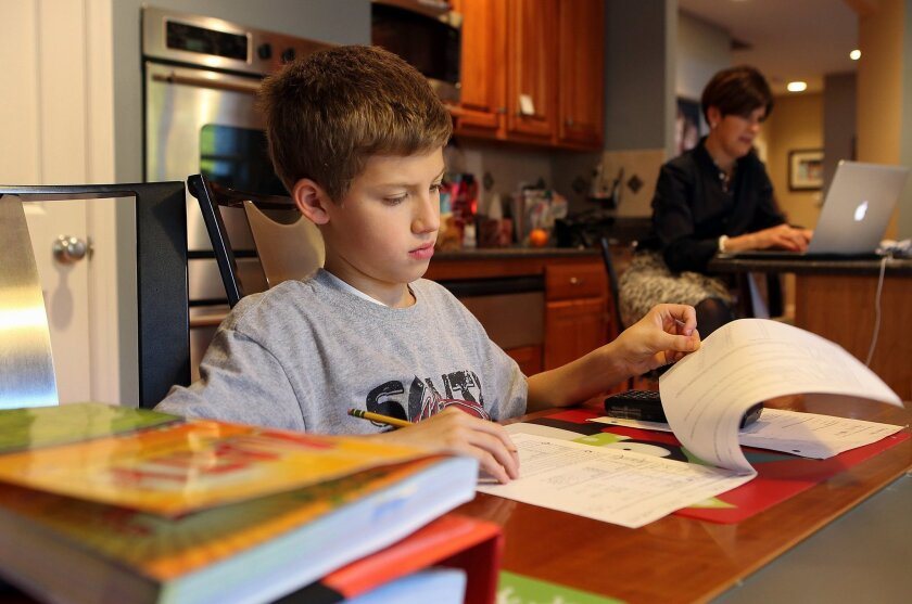 Sixth-grader Kyle Stilwell, 12, works on his pre-algebra study guide as mom Niki works from home in Fenton, Mo.