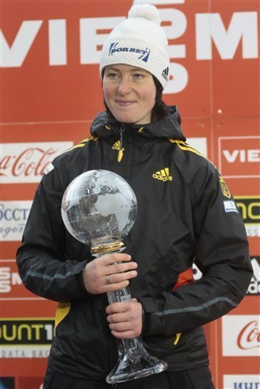 World Cup Winner Marion Thees of Germany poses with her trophy on the podium during the FIBT Bob & Skeleton World Cup 2013, in Krasnaya Polyana resort, some 60 km east of Sochi, Russia, Saturday, Feb. 16, 2013. Thees took the forth placed in the women skeleton events. (AP Photo/Mikhail Metzel)