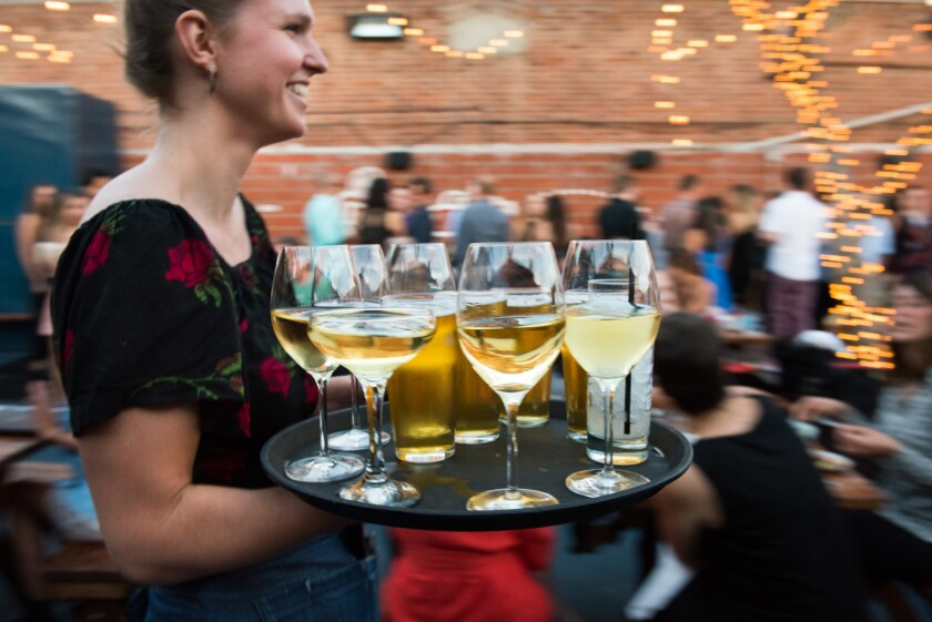 A server brings a tray of drinks to the patio at Everson Royce Bar.