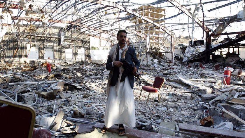 TOPSHOT - A Yemeni man stands on October 24, 2016 at the site of an air raid on a funeral ceremony t