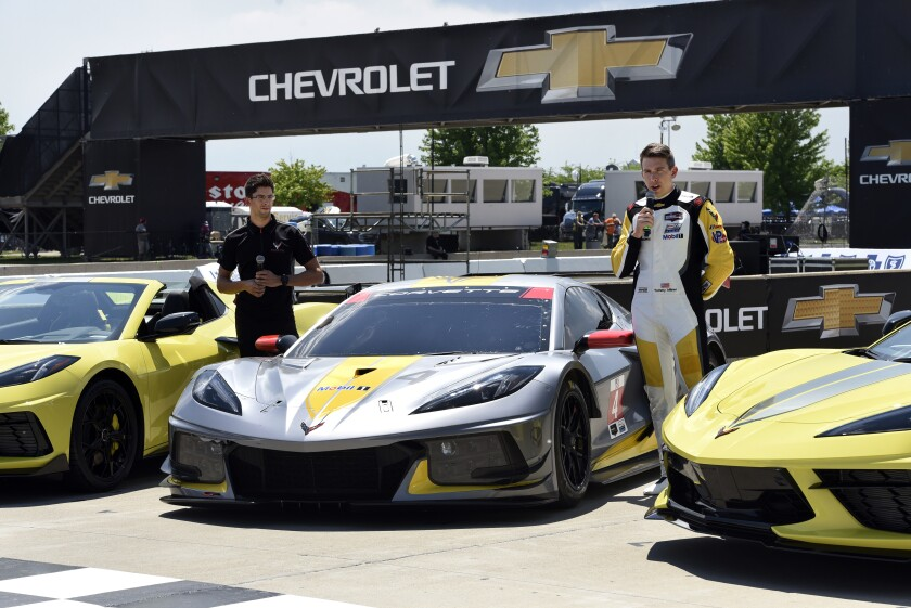 Drivers Jordan Taylor, left, and Tommy Milner attend a news conference while standing next to a Corvette C8.R race car Wednesday, June 9, 2021, at Raceway at Belle Isle in Detroit. (AP Photo/Jose Juarez)