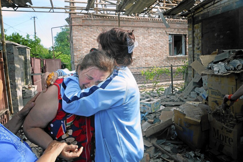 Ekaterina Len, left, is overcome with emotion after her house was damaged by a shell during fighting between pro-Russia separatists and Ukrainian troops in Slovyansk.