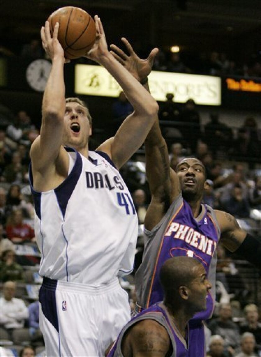 Dallas Mavericks forward Dirk Nowitzki (41,) of Germany, attempts a shot over Phoenix Suns guard Raja Bell, lower right, as forward Amare Stoudemire, upper right, defends in the first half of an NBA basketball game in Dallas, Thursday, Dec. 4, 2008. (AP Photo/Tony Gutierrez)