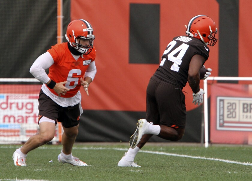 Cleveland Browns' Baker Mayfield (6) hands off the ball to Nick Chubb (24) during drills at NFL football practice Sunday, Aug. 16, 2020, in Berea, Ohio. (David Petkiewicz/The Plain Dealer via AP)