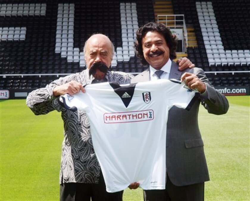 Mohamed Al Fayed, left, wearing a fake mustache, with new Fulham owner Shahid Khan, during a photo call at Craven Cottage, London, Saturday July 13, 2013.(AP Photo/PA, Max Nash)UNITED KINGDOM OUT NO ARCHIVE NO SALES
