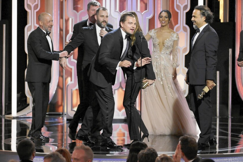 """Leonardo DiCaprio, center, and director Alejandro G. Iñárritu, right, celebrate """"The Revenant's"""" big wins for lead actor, director and motion picture drama."""