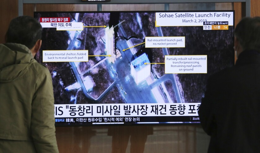 People in Seoul watch a TV screen showing an image of a North Korean rocket launch station.