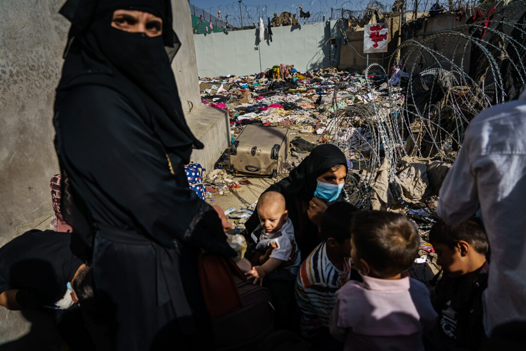 A woman in a black burqa next to women and children crouching near barbed wire