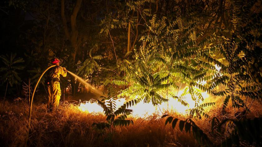 A firefighter works to defend structures on Lytle Creek Road on Wednesday night.