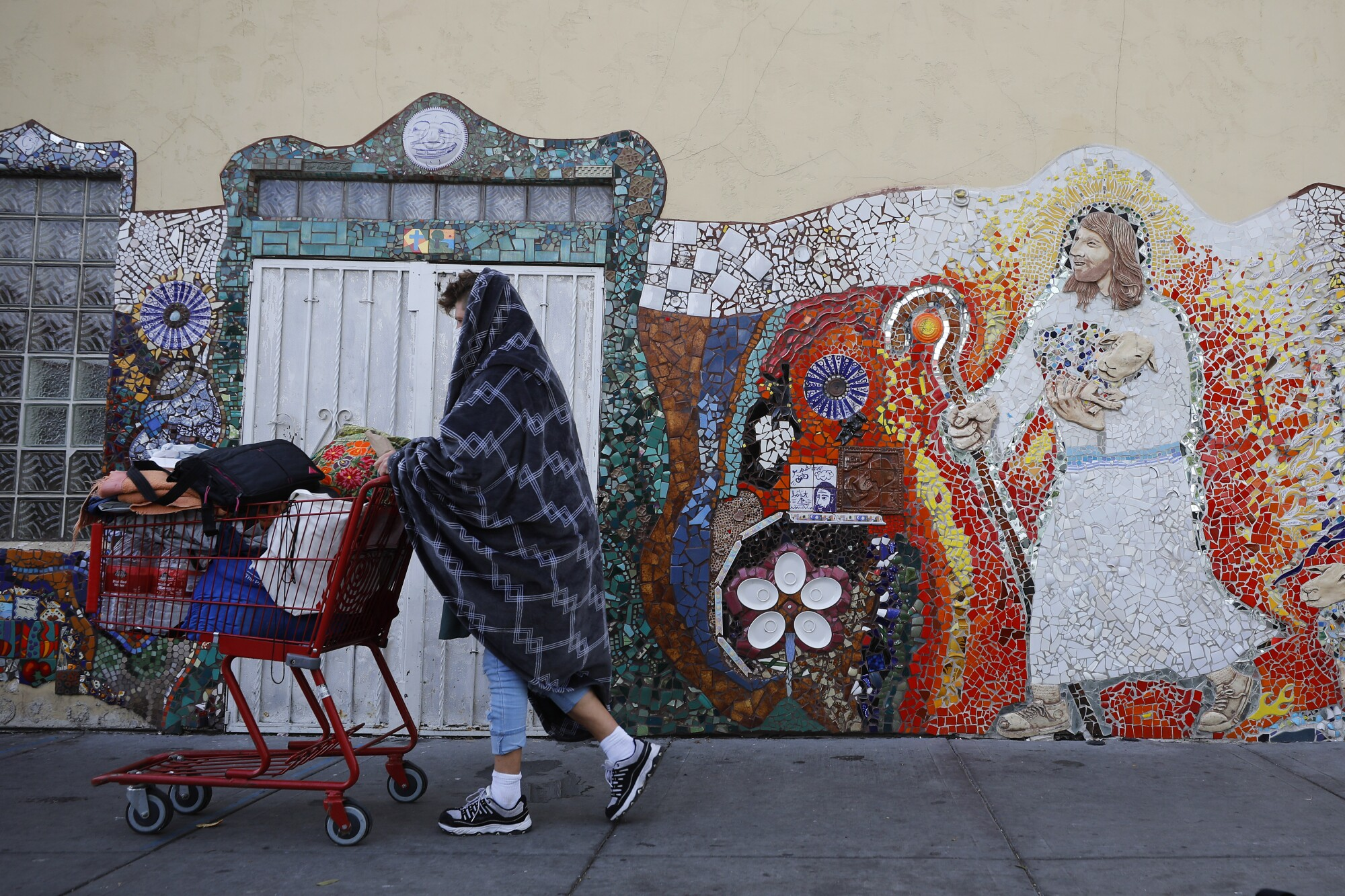 A woman walks past God's Extended Hand ministry, which has served homeless people in downtown San Diego almost 100 years.