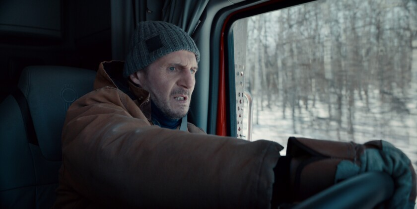 Liam Neeson, with a beanie on his head and a look of fear on his face, drives a truck amid a snowy landscape.