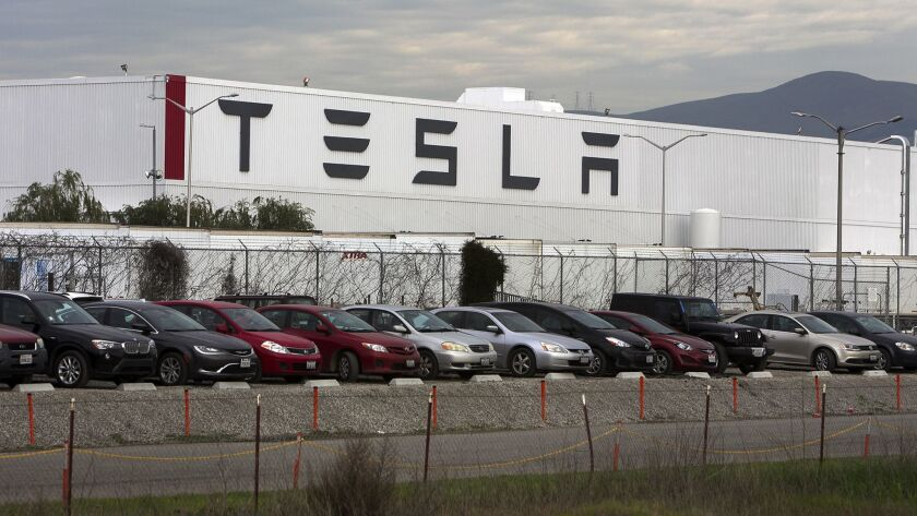 Cars are lined up near the Tesla Motors factory complex in Fremont, Calif., in 2016.