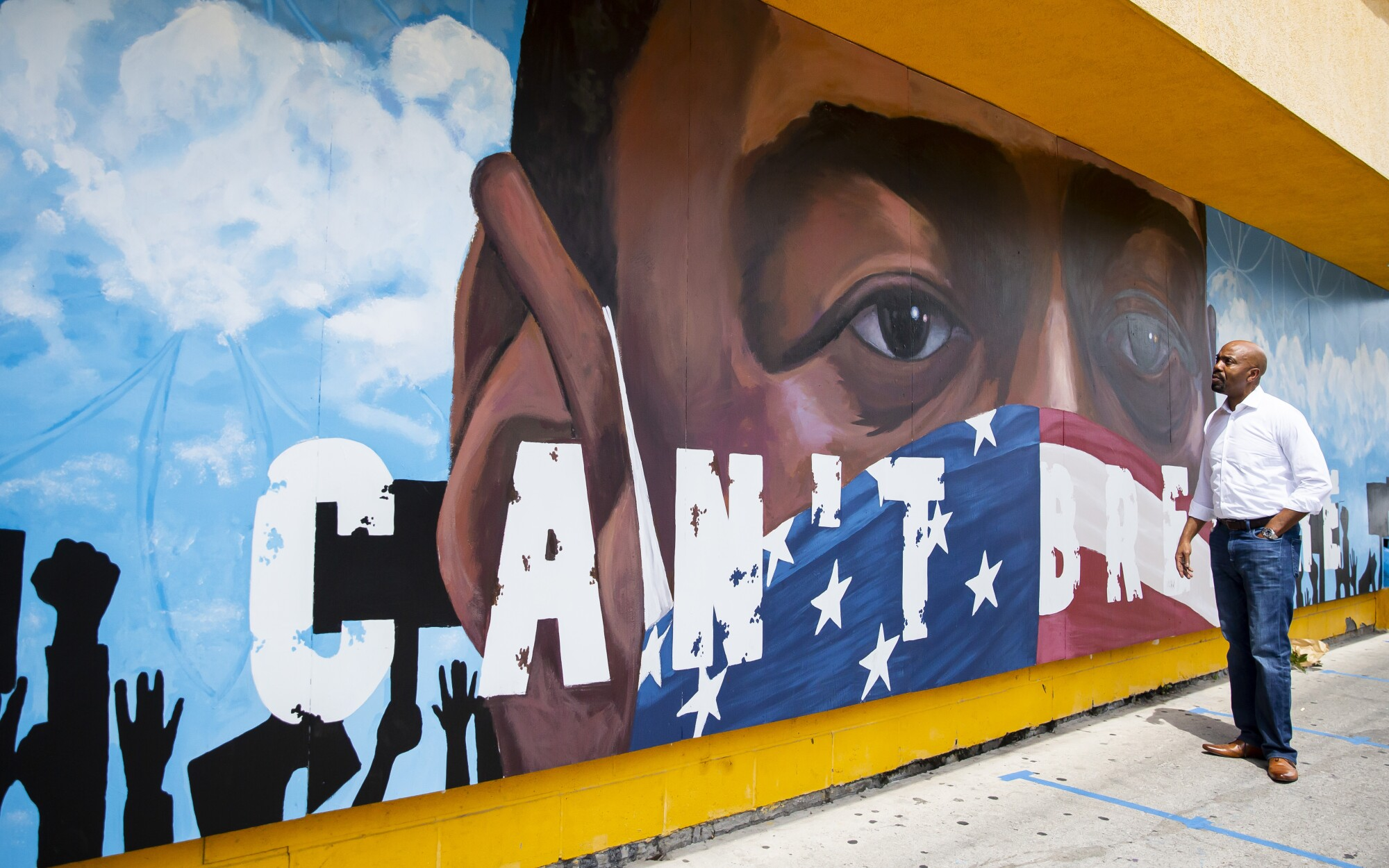 Civil rights attorney Daryl Washington admires a mural of George Floyd painted on the side of the Breakfast Klub in Houston.