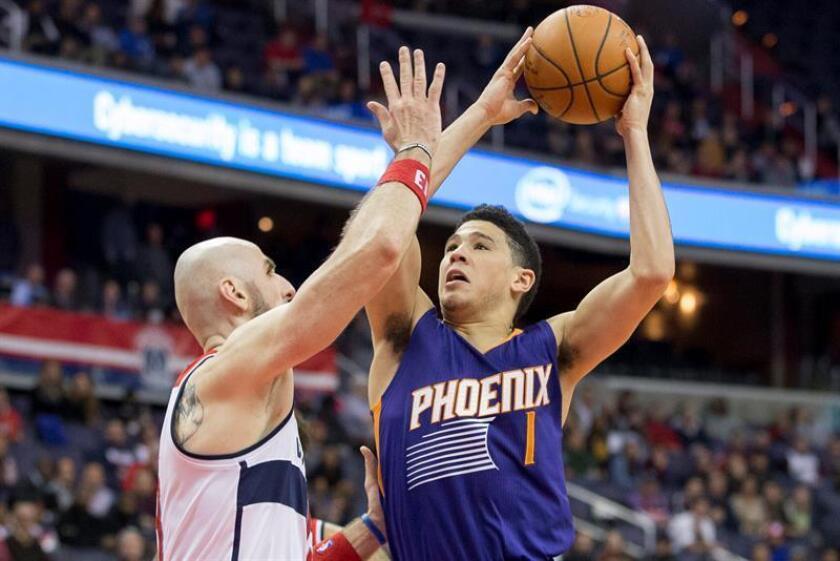 Devin Booker (d) de Phoenix Suns salta para lanzar durante un juego de la NBA. EFE/Archivo
