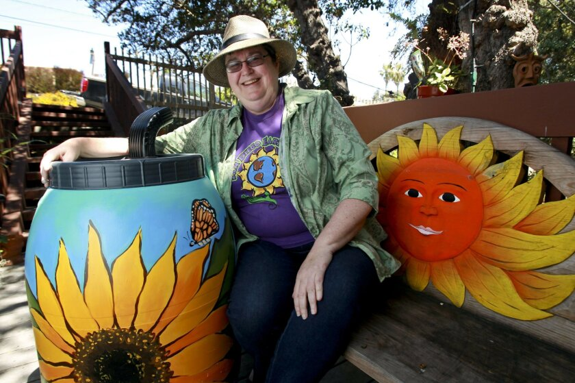 EarthFair organizer Carolyn Chase with her new rain barrel, which originally was a 50 gallon olive barrel from Italy destined for the dump, at her Pacific Beach home in San Diego on Wednesday.