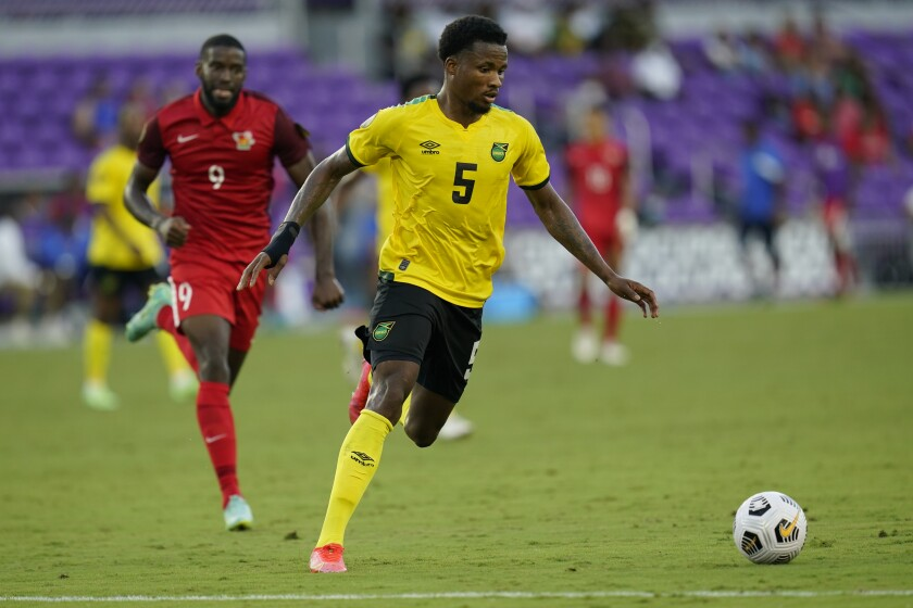Jamaica defender Alvas Powell moves the ball ahead of Guadeloupe forward Raphael Mirval.
