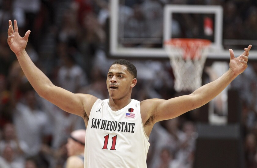 The Aztecs' Matt Mitchell puts his arms out as he celebrates the Aztecs' lead over Utah State during the second half at the Viejas Arena on Saturday. Mitchell had 28 points, 24 in the second half as San Diego State rallied to the victory.