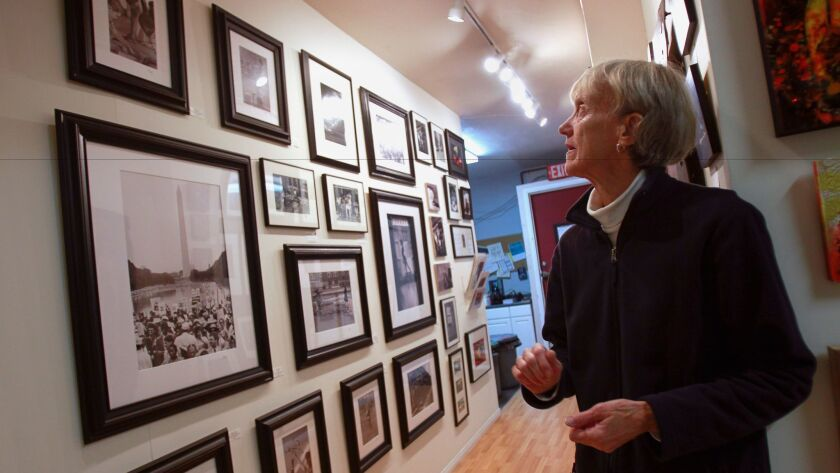 Anne-Grethe Morris, wife of late photographer and educator Major Morris, looks at his photographs at the Distinction Gallery in Escondido on Thursday.