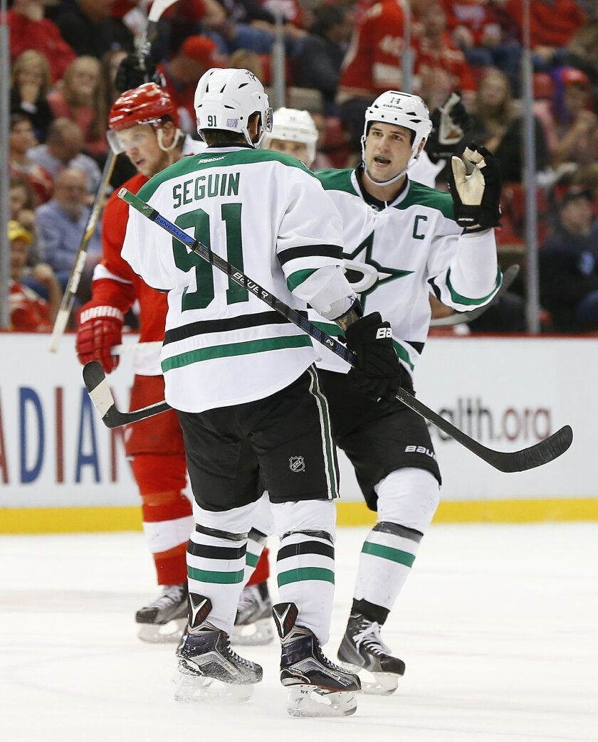 Dallas Stars left wing Jamie Benn, right, celebrates Tyler Seguin's (91) empty net goal against the Detroit Red Wings in the third period of an NHL hockey game, Sunday, Nov. 8, 2015 in Detroit. Dallas won 4-1. (AP Photo/Paul Sancya)