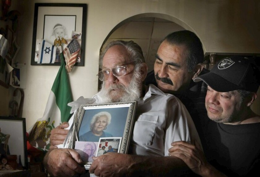 Eddie Goldstein holds a photo of his late wife, Esther. They were married 50 years and raised their kids, including Art Perez, center, and Steven Goldstein, on Folsom Street.