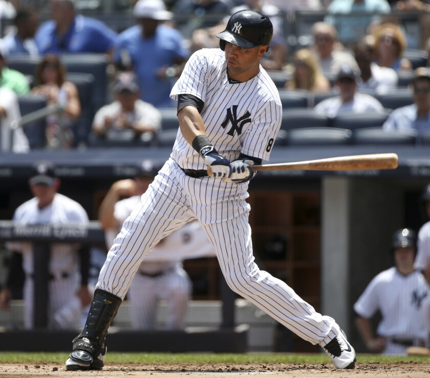 Yankees outfielder Carlos Beltran hits a solo home run during the first inning against the Giants on July 24.