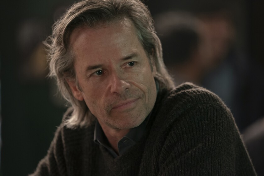Guy Pearce in a brown sweater with long, graying hair