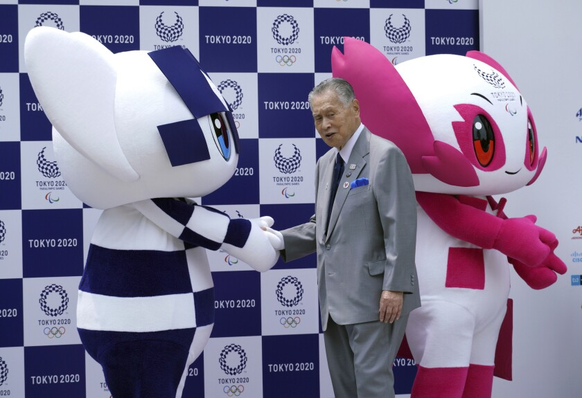 A man in a suit and tie shakes the hand of one of two people in mascot costumes.