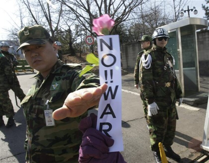 A South Korean army soldier gestures as an anti-war protester gives a flower to him during a rally against South Korean activists who launched propaganda leaflets toward North Korea, at a main gate of Defense Ministry in Seoul, South Korea, Wednesday, March 2, 2011. South Korean activists say they