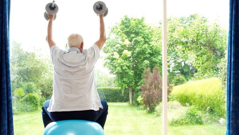 Man lifting weights at home. CREDIT: Photographer: PhotoConcepts / Getty Images