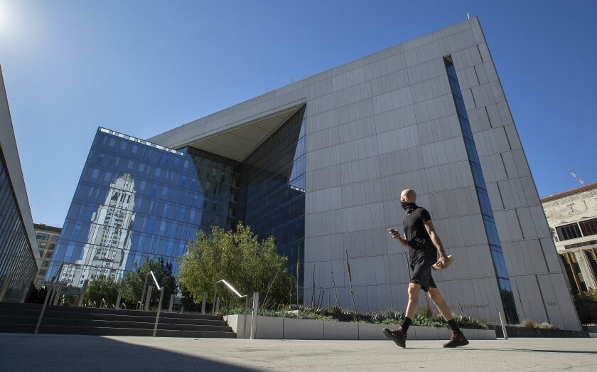 A masked pedestrian walks in front of LAPD headquarters in downtown Los Angeles.