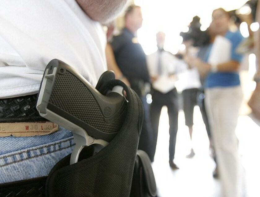 A man wears a gun at a North County open-carry gathering in the summer of 2009.