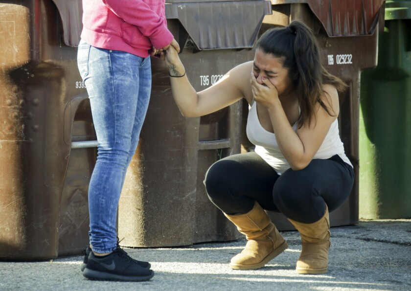 A woman weeps after hearing that her boyfriend was one of three men found fatally shot in a room at Raymond Street Park.