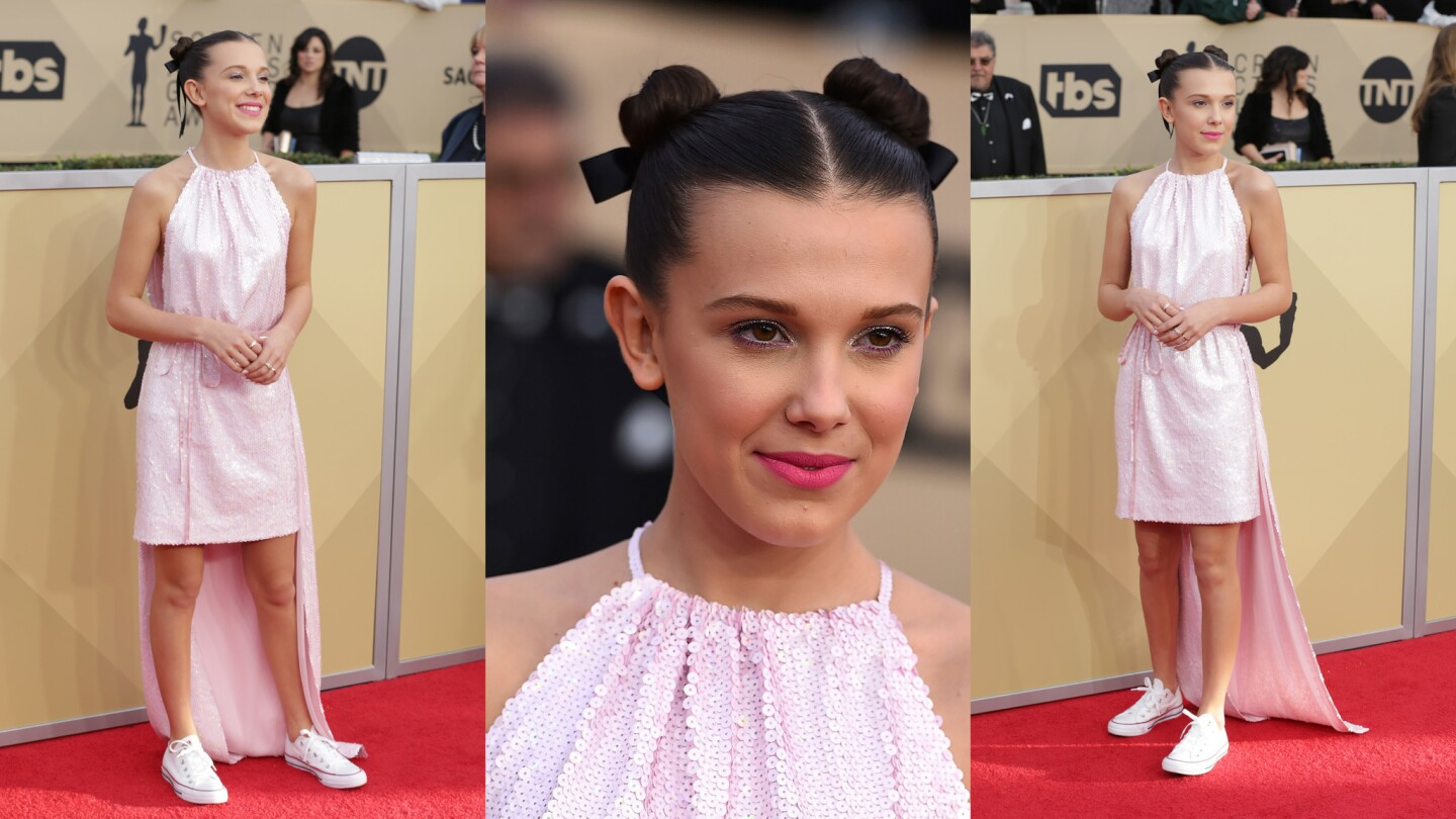 """The high-low hem of Millie Bobby Brown's Calvin Klein dress gives it a cape-like feel making the """"Stranger Things"""" star one of the evening's sartorial superheroes."""