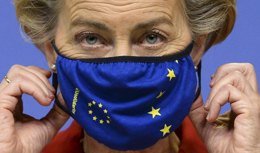 European Commission President Ursula von der Leyen, prepares to take off her protective mask, prior to making a statement regarding the Withdrawal Agreement at EU headquarters in Brussels, Thursday, Oct. 1, 2020. The European Union took legal action against Britain on Thursday over its plans to pass legislation that would breach parts of the legally binding divorce agreement the two sides reached late last year. (Johanna Geron, Pool via AP)