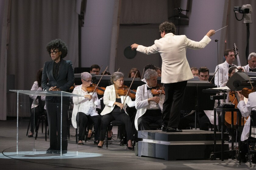 A man in a white jacket conducts members of an orchestra, also wearing white jackets, while a woman in black is at a podium.